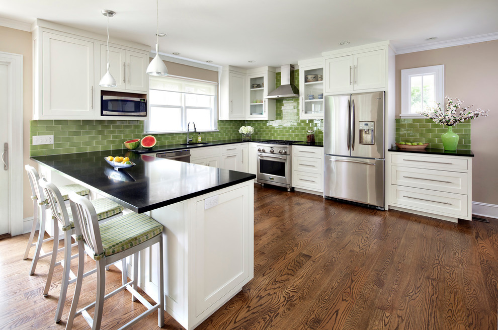 U-shaped eat-in kitchen photo in New York with stainless steel appliances, an undermount sink, shaker cabinets, white cabinets, granite countertops, green backsplash and ceramic backsplash