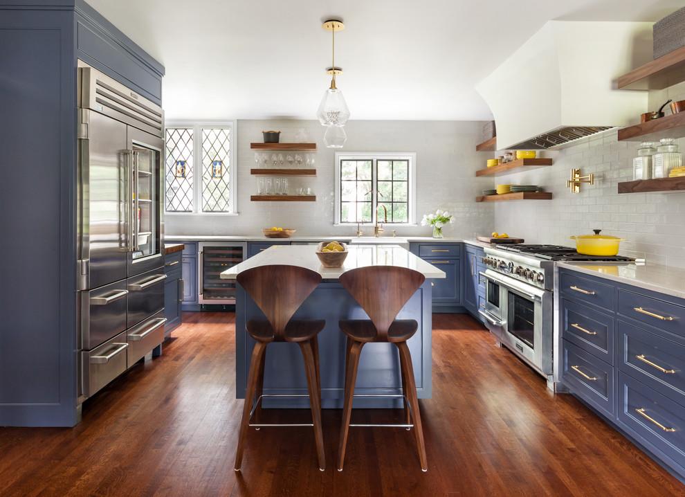 Klassisk inredning av ett vit vitt u-kök, med en rustik diskho, luckor med infälld panel, lila skåp, vitt stänkskydd, rostfria vitvaror, mellanmörkt trägolv, en köksö och brunt golv