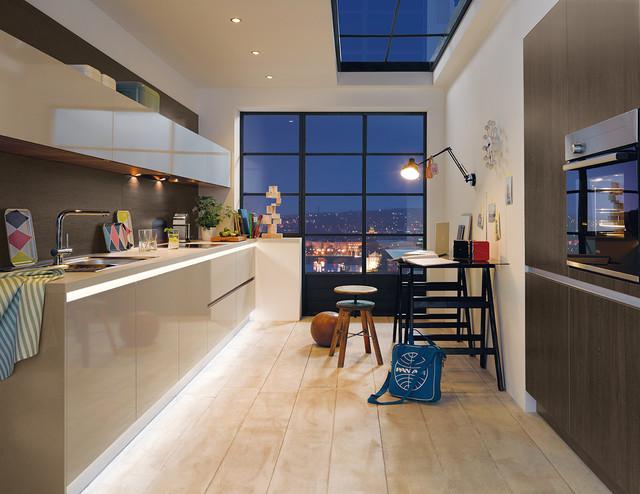 Foto de cocina de galera, actual, de tamaño medio, cerrada, con armarios con paneles lisos, puertas de armario beige y suelo de madera clara