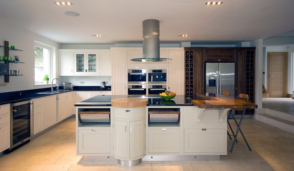 Inspiration for a contemporary kitchen remodel in Manchester with recessed-panel cabinets, stainless steel appliances and wood countertops