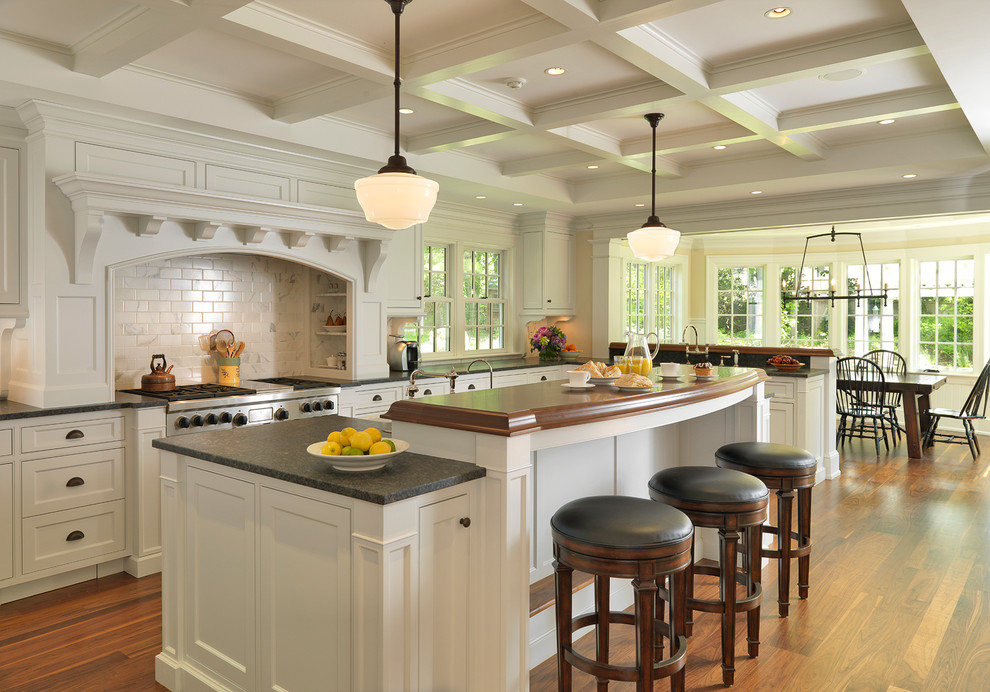 Example of a classic kitchen design in Boston with subway tile backsplash and wood countertops