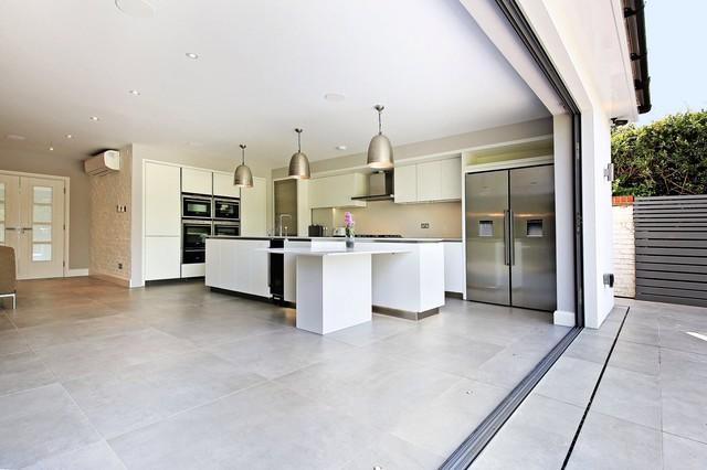 Foto på ett funkis kök, med släta luckor, vita skåp, beige stänkskydd, rostfria vitvaror och en köksö