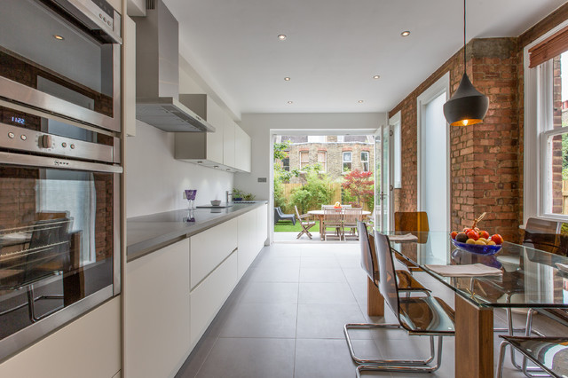 This is an example of a contemporary single-wall kitchen/diner in London with a submerged sink, flat-panel cabinets, white cabinets, stainless steel appliances and no island.