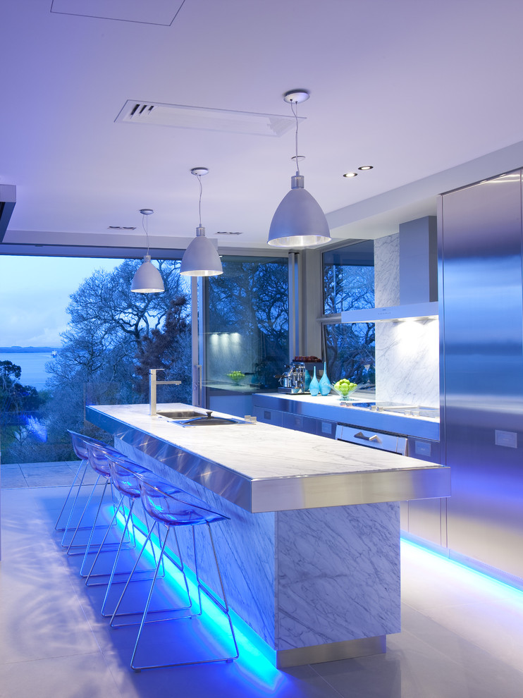 Inspiration for a large contemporary galley eat-in kitchen remodel in Los Angeles with stainless steel appliances, flat-panel cabinets, stainless steel cabinets, white backsplash, stainless steel countertops, marble backsplash and an island