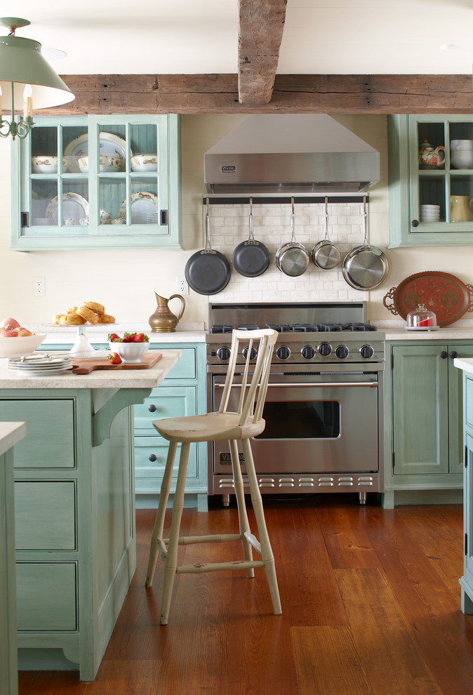 Inspiration for a mid-sized country u-shaped medium tone wood floor eat-in kitchen remodel in New York with beaded inset cabinets, granite countertops, white backsplash, ceramic backsplash, stainless steel appliances, an island and green cabinets