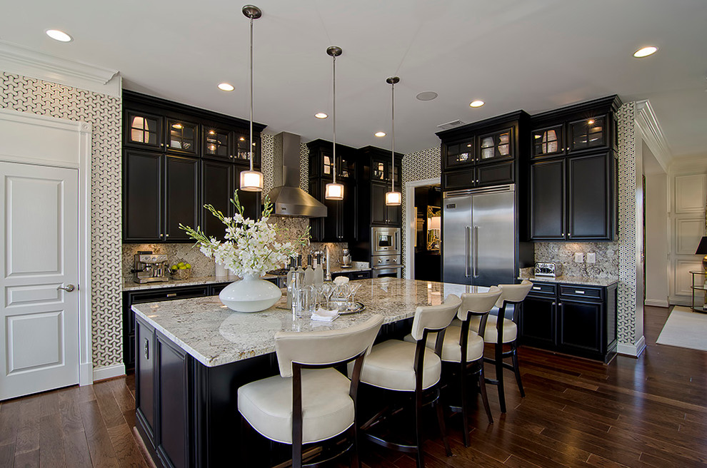 Example of a classic kitchen design in DC Metro with stainless steel appliances, black cabinets and white backsplash
