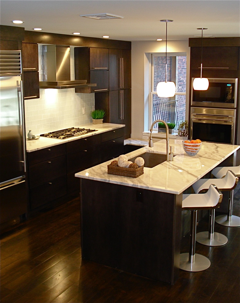 Inspiration for a contemporary galley kitchen remodel in Boston with stainless steel appliances, marble countertops, an undermount sink, flat-panel cabinets, dark wood cabinets, white backsplash and subway tile backsplash