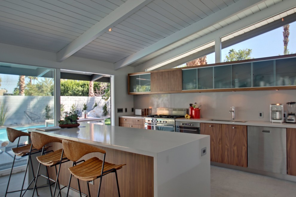 Example of a mid-sized trendy single-wall concrete floor eat-in kitchen design in Los Angeles with a double-bowl sink, flat-panel cabinets, medium tone wood cabinets, white backsplash, stainless steel appliances and an island