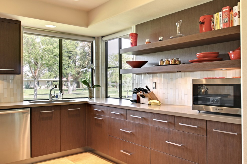 Example of a mid-sized 1960s l-shaped eat-in kitchen design in Los Angeles with a double-bowl sink, flat-panel cabinets, medium tone wood cabinets, white backsplash and stainless steel appliances