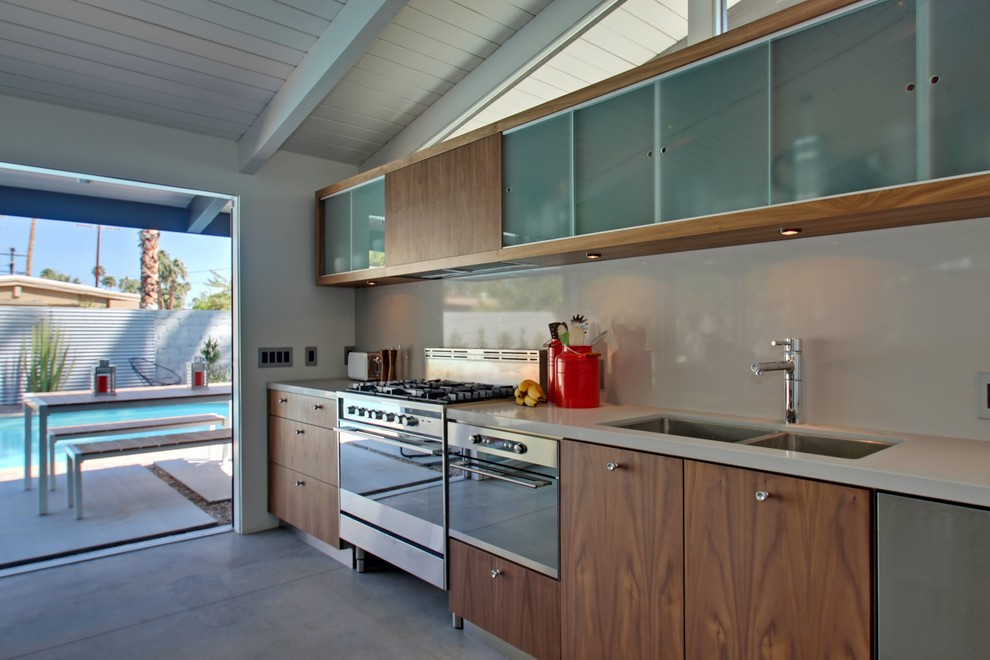 Eat-in kitchen - mid-sized contemporary single-wall concrete floor eat-in kitchen idea in Los Angeles with a double-bowl sink, flat-panel cabinets, medium tone wood cabinets, white backsplash, stainless steel appliances and an island