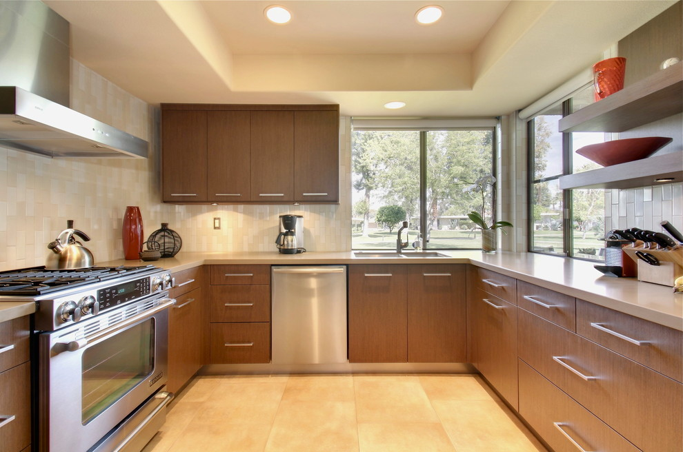 Mid-sized 1960s l-shaped eat-in kitchen photo in Los Angeles with flat-panel cabinets, medium tone wood cabinets and white backsplash