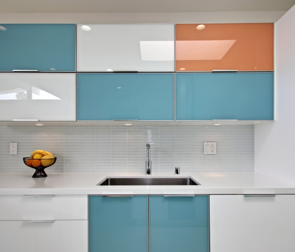 Example of a small minimalist l-shaped eat-in kitchen design in Los Angeles with flat-panel cabinets, white cabinets, white backsplash and a peninsula