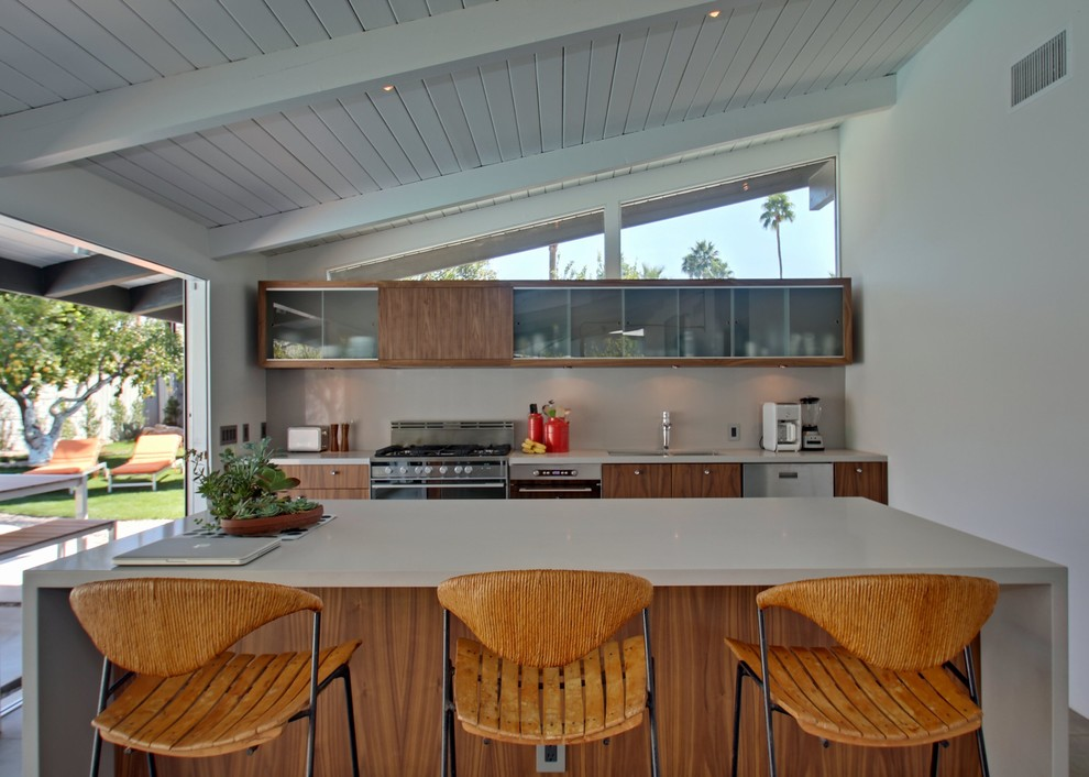 Mid-sized trendy single-wall concrete floor eat-in kitchen photo in Los Angeles with a double-bowl sink, flat-panel cabinets, medium tone wood cabinets, white backsplash, stainless steel appliances and an island