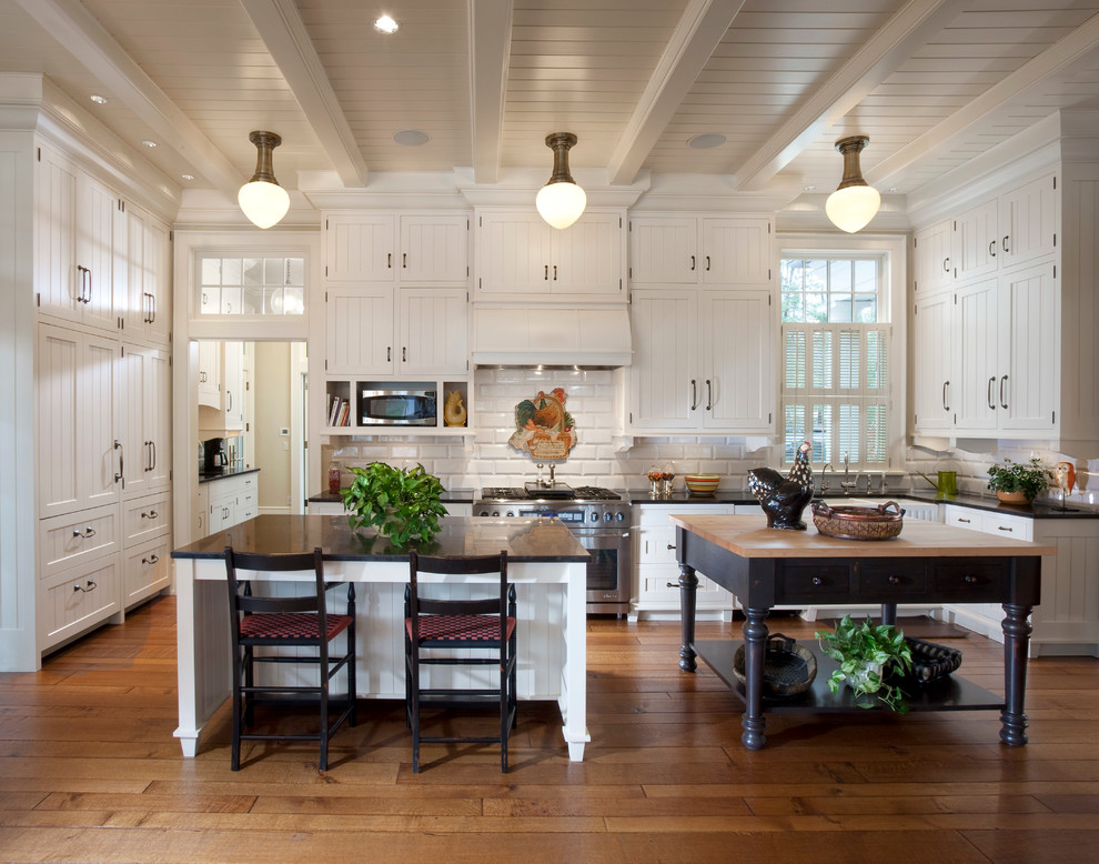 Country medium tone wood floor kitchen photo in Milwaukee with a farmhouse sink, recessed-panel cabinets, white cabinets, white backsplash, stainless steel appliances and two islands