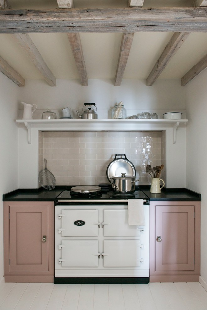 Example of a farmhouse painted wood floor kitchen design in London with shaker cabinets, white appliances and no island