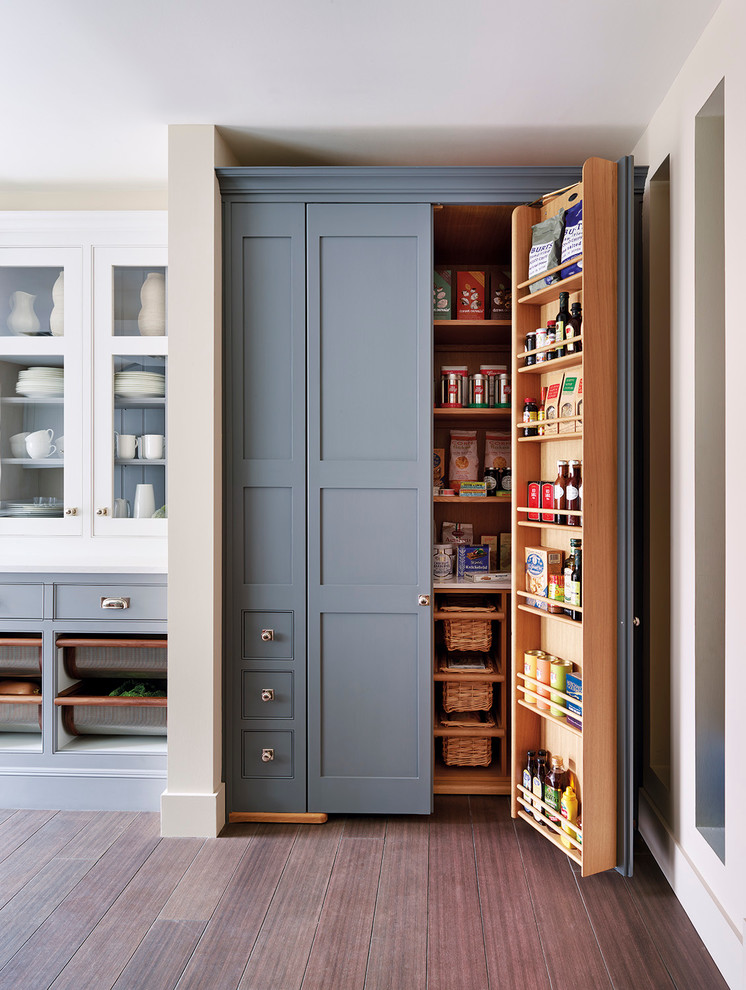 Example of a classic medium tone wood floor kitchen pantry design in London with shaker cabinets and gray cabinets