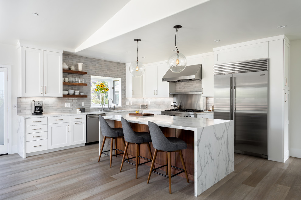 Transitional l-shaped medium tone wood floor and gray floor kitchen photo in San Diego with an undermount sink, shaker cabinets, white cabinets, gray backsplash, stainless steel appliances, an island and white countertops