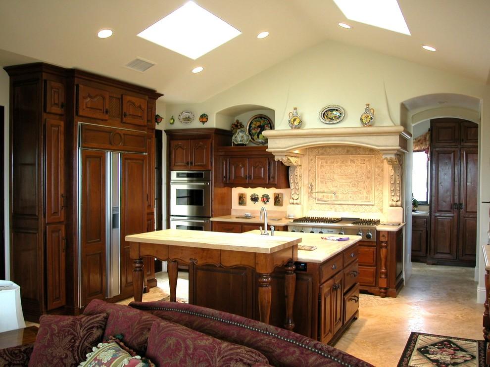 Imagen de cocina clásica, abierta, con electrodomésticos con paneles y puertas de armario de madera en tonos medios