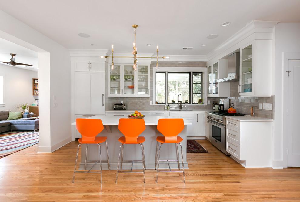 Idee per una cucina a L classica con lavello sottopiano, ante di vetro, ante bianche, paraspruzzi grigio, elettrodomestici in acciaio inossidabile, pavimento in legno massello medio e isola