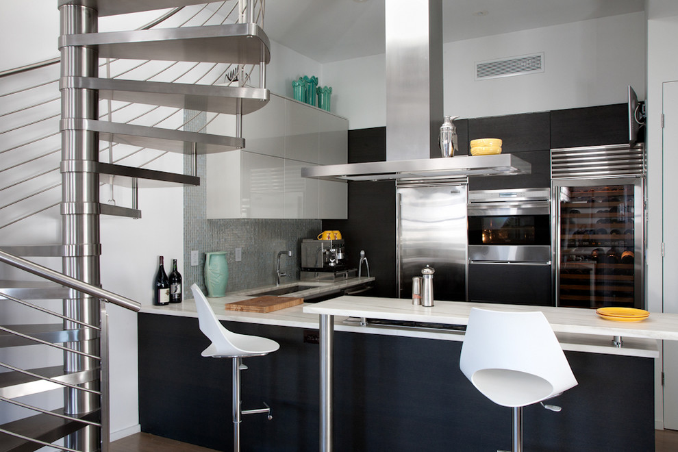 Kitchen - industrial kitchen idea in New York with stainless steel appliances, flat-panel cabinets and black cabinets