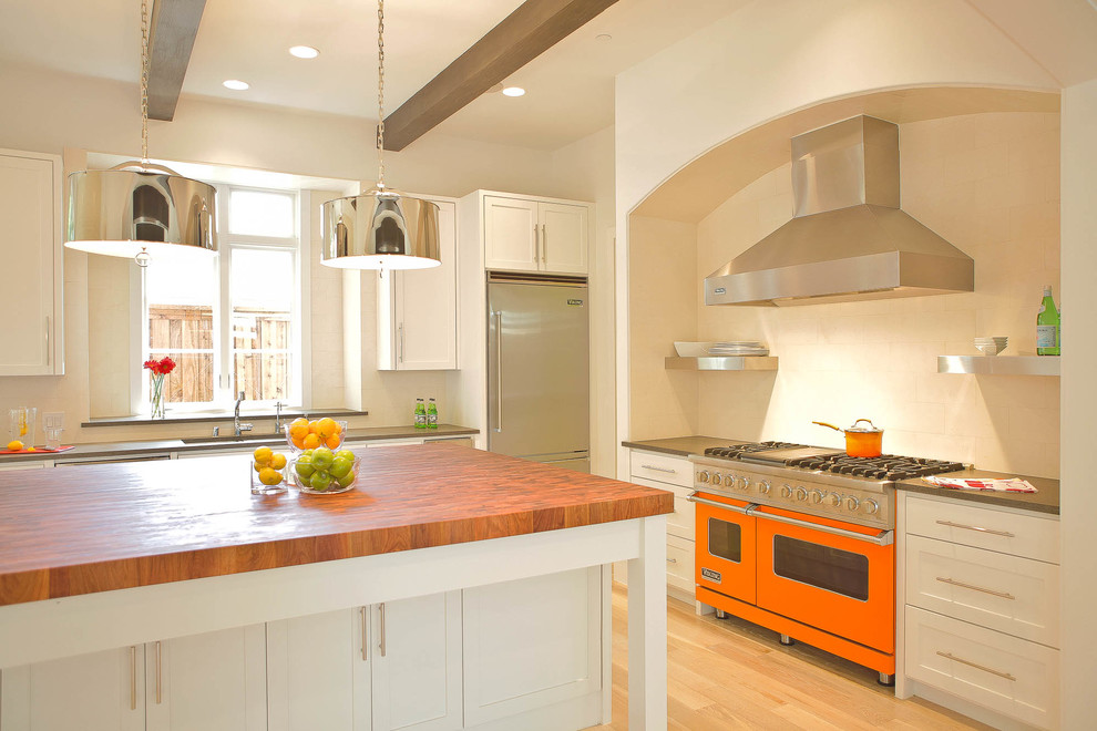Inspiration for a contemporary l-shaped kitchen remodel in Dallas with white cabinets, wood countertops, colored appliances, shaker cabinets and beige backsplash