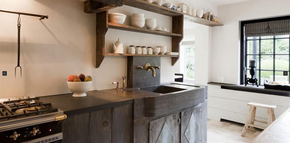 Kitchen - transitional limestone floor kitchen idea in New York with a farmhouse sink, open cabinets, distressed cabinets, black appliances, soapstone countertops, black backsplash and stone slab backsplash
