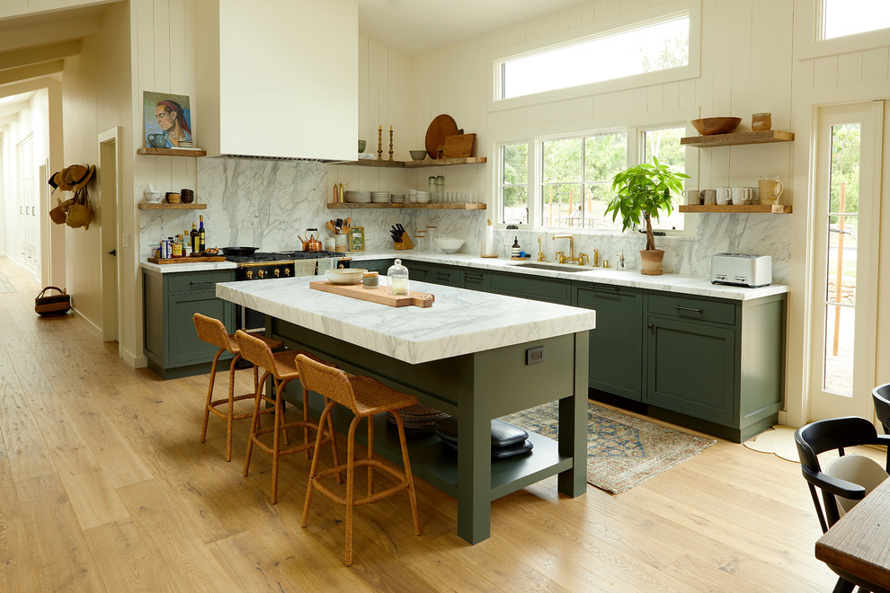 Inspiration for a farmhouse l-shaped medium tone wood floor and brown floor eat-in kitchen remodel in Santa Barbara with an undermount sink, shaker cabinets, green cabinets, white backsplash, stone slab backsplash, black appliances and an island