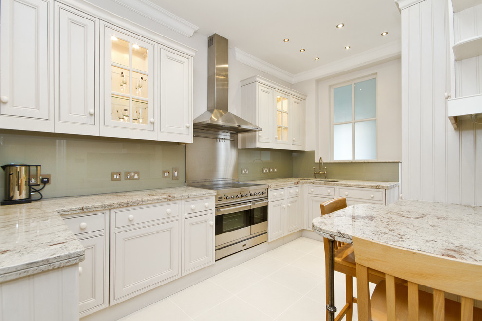 Inspiration for a transitional kitchen remodel in London with beaded inset cabinets, stainless steel appliances, white cabinets, green backsplash and glass sheet backsplash