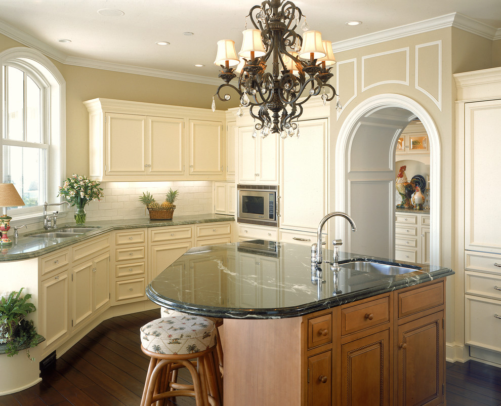 Large french country u-shaped dark wood floor enclosed kitchen photo in San Diego with a double-bowl sink, recessed-panel cabinets, beige cabinets, white backsplash, subway tile backsplash, paneled appliances, marble countertops and an island