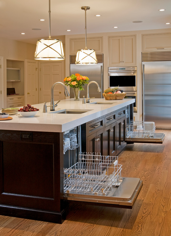 Example of a large classic u-shaped medium tone wood floor kitchen design in Philadelphia with an undermount sink, recessed-panel cabinets, dark wood cabinets, stainless steel appliances, solid surface countertops and an island