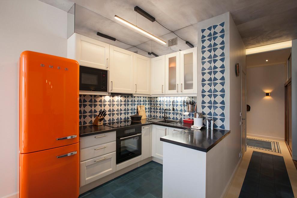Создайте стильный интерьер: п-образная кухня - столовая в современном стиле с накладной раковиной, фасадами в стиле шейкер, белыми фасадами, разноцветным фартуком, черной техникой и полуостровом - последний тренд
