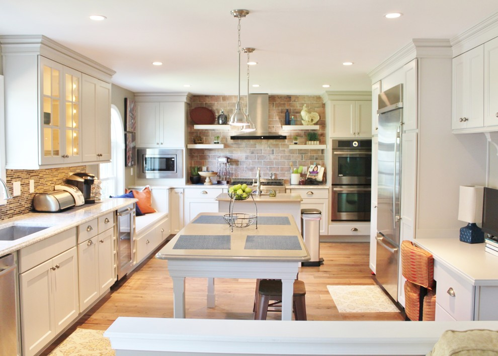 Large transitional u-shaped medium tone wood floor kitchen photo in Philadelphia with a double-bowl sink, shaker cabinets, white cabinets, quartz countertops, brown backsplash, mosaic tile backsplash, stainless steel appliances and two islands