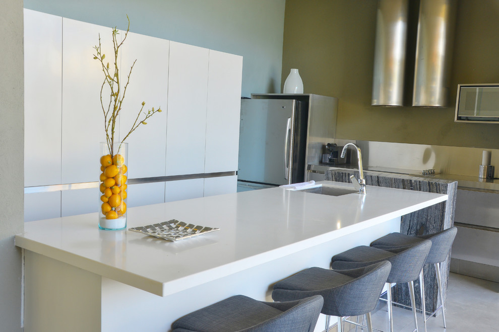 Inspiration for a small modern single-wall open concept kitchen remodel in Los Angeles with flat-panel cabinets, white cabinets, quartz countertops, metallic backsplash and an island