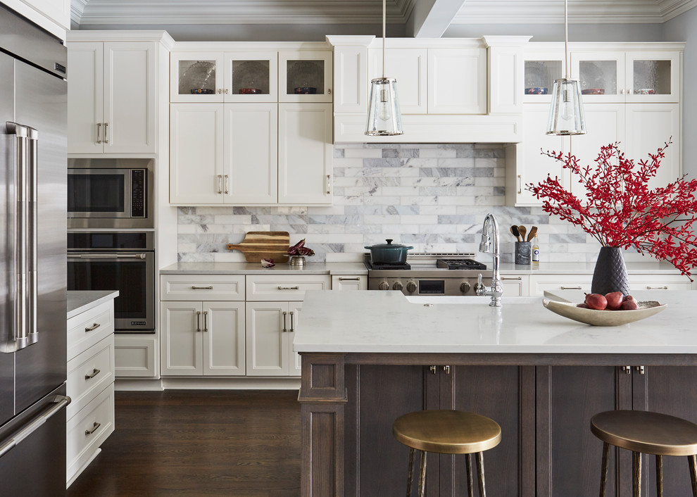 Inspiration for a large transitional l-shaped brown floor and dark wood floor kitchen remodel in Chicago with a farmhouse sink, shaker cabinets, white cabinets, quartz countertops, marble backsplash, stainless steel appliances, an island, multicolored backsplash and gray countertops
