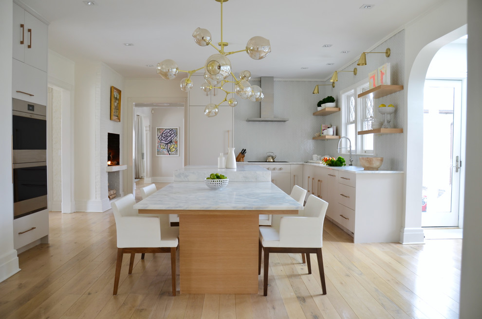 Mid-sized transitional l-shaped light wood floor and beige floor eat-in kitchen photo in New York with flat-panel cabinets, white cabinets, gray backsplash, stainless steel appliances, an island, an undermount sink, marble countertops and ceramic backsplash