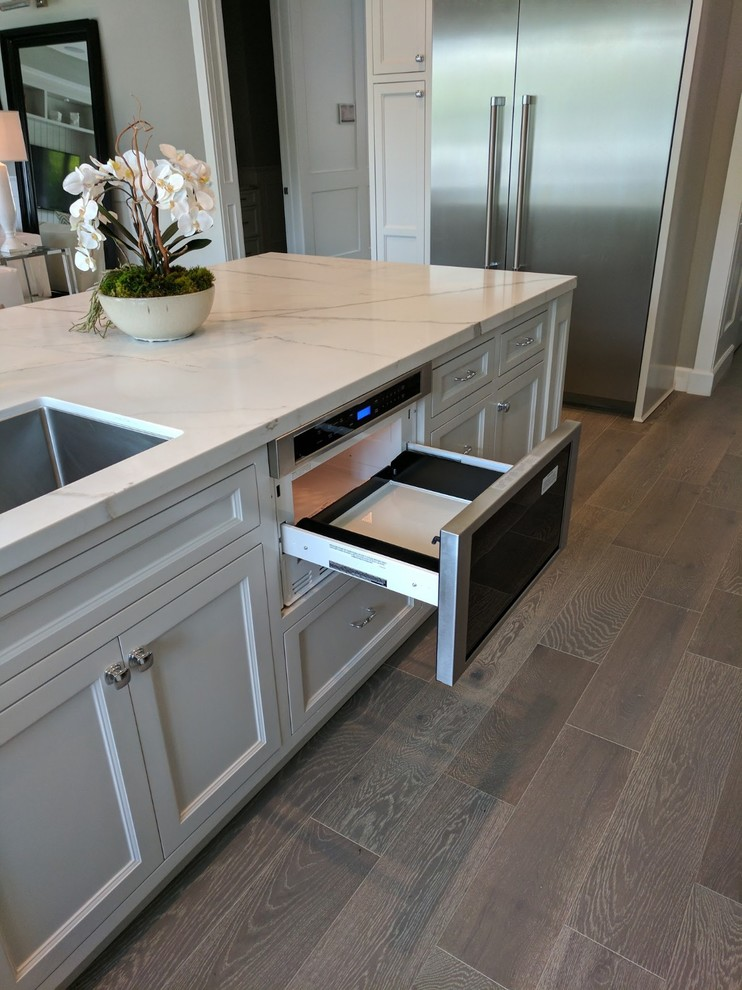 Example of a large minimalist u-shaped porcelain tile, gray floor and exposed beam eat-in kitchen design in Orange County with an undermount sink, recessed-panel cabinets, white cabinets, quartz countertops, white backsplash, stone slab backsplash, stainless steel appliances, an island and white countertops