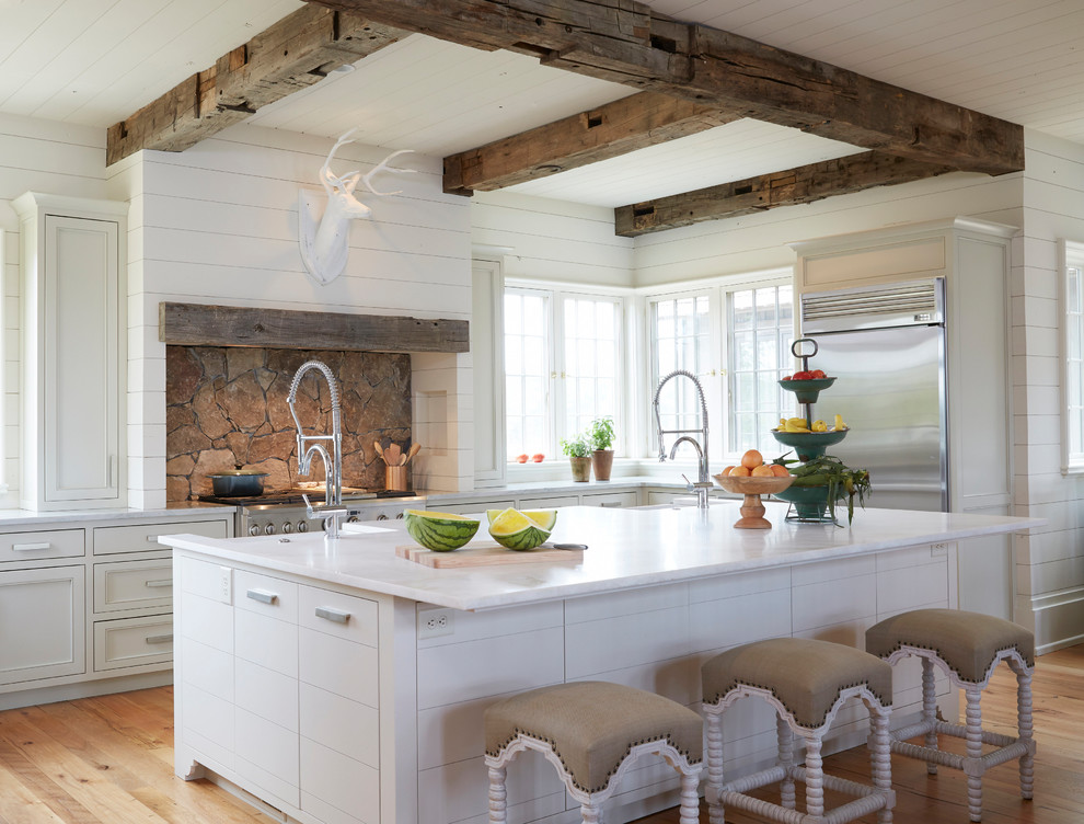 Coastal l-shaped medium tone wood floor and brown floor kitchen photo in Birmingham with a farmhouse sink, beaded inset cabinets, white cabinets, stainless steel appliances and an island