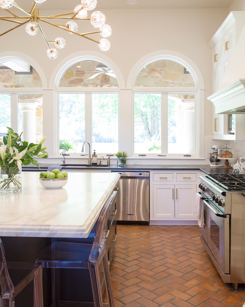 Example of a large transitional u-shaped brick floor kitchen design in Austin with an undermount sink, shaker cabinets, white cabinets, marble countertops, white backsplash, subway tile backsplash, stainless steel appliances, an island and black countertops