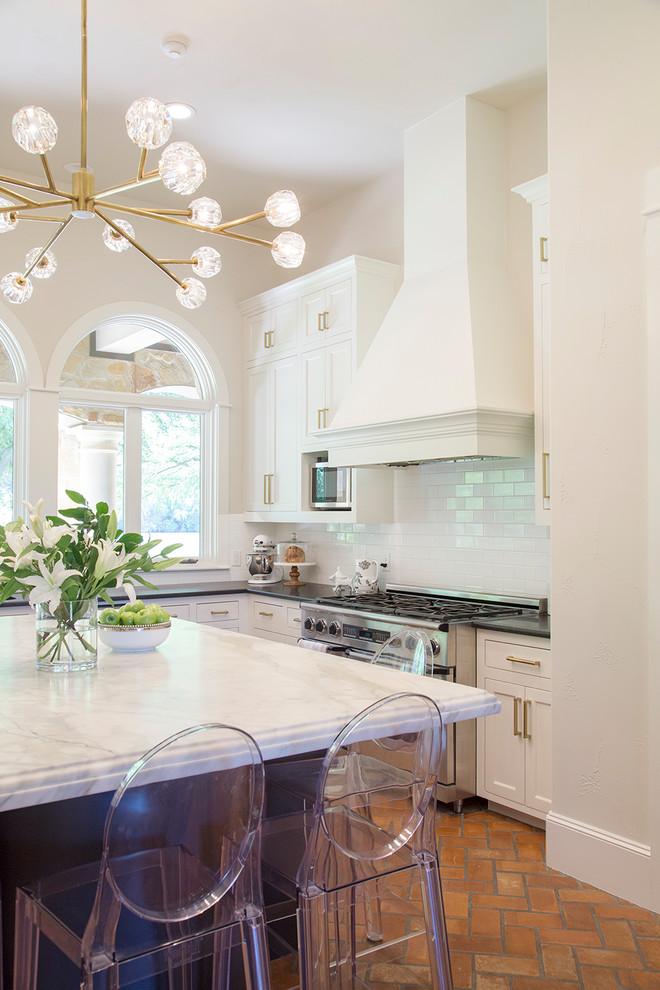 Kitchen - huge transitional u-shaped brick floor kitchen idea in Austin with white cabinets, marble countertops, white backsplash, subway tile backsplash, stainless steel appliances and an island