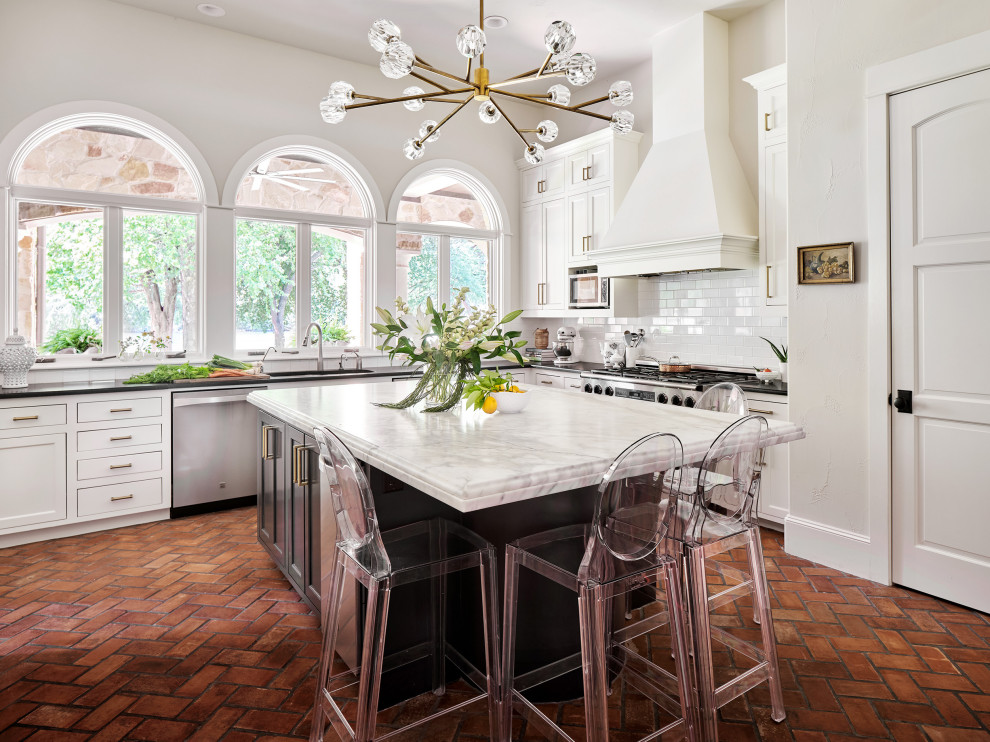 Kitchen - huge traditional u-shaped brick floor kitchen idea in Austin with an undermount sink, shaker cabinets, white cabinets, marble countertops, white backsplash, subway tile backsplash, stainless steel appliances and an island