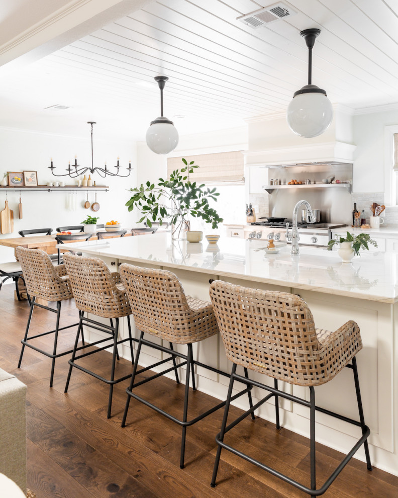 Open concept kitchen - mid-sized transitional medium tone wood floor and brown floor open concept kitchen idea in Dallas with white cabinets, quartzite countertops, white backsplash, terra-cotta backsplash, stainless steel appliances, an island and white countertops
