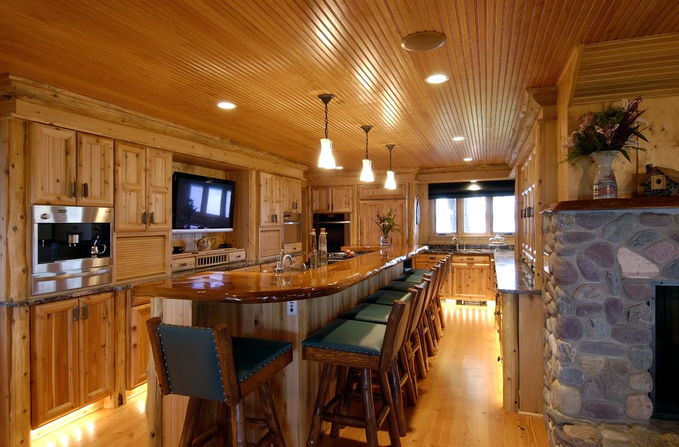 Elegant kitchen photo in Minneapolis with recessed-panel cabinets, medium tone wood cabinets and paneled appliances