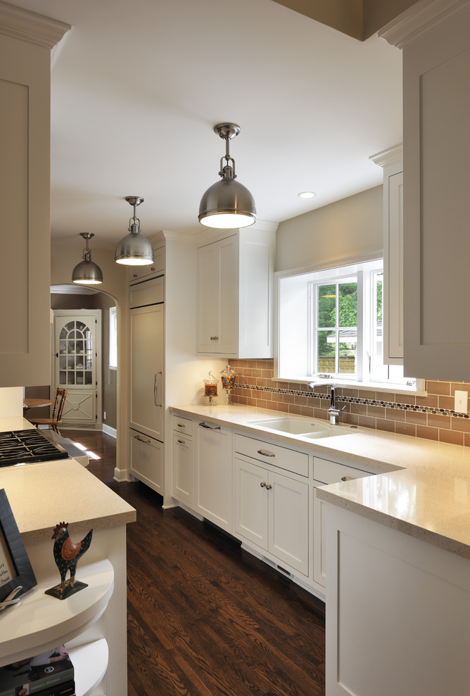 Elegant galley kitchen photo in Minneapolis with an undermount sink, shaker cabinets, white cabinets, brown backsplash, subway tile backsplash and paneled appliances