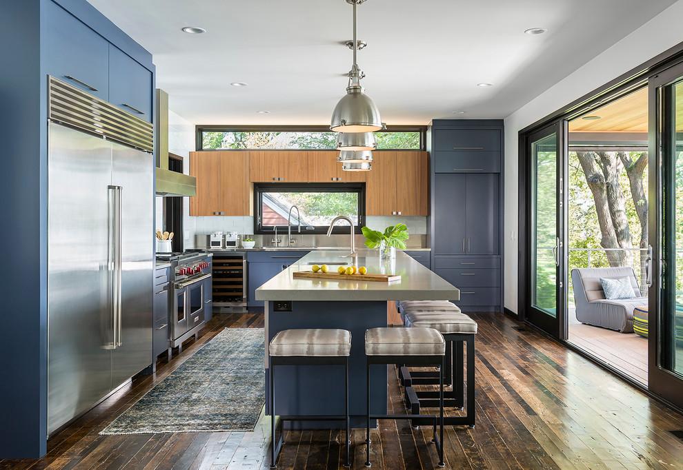 Foto di una cucina minimal con lavello integrato, ante lisce, ante blu, top in acciaio inossidabile, elettrodomestici in acciaio inossidabile e parquet scuro