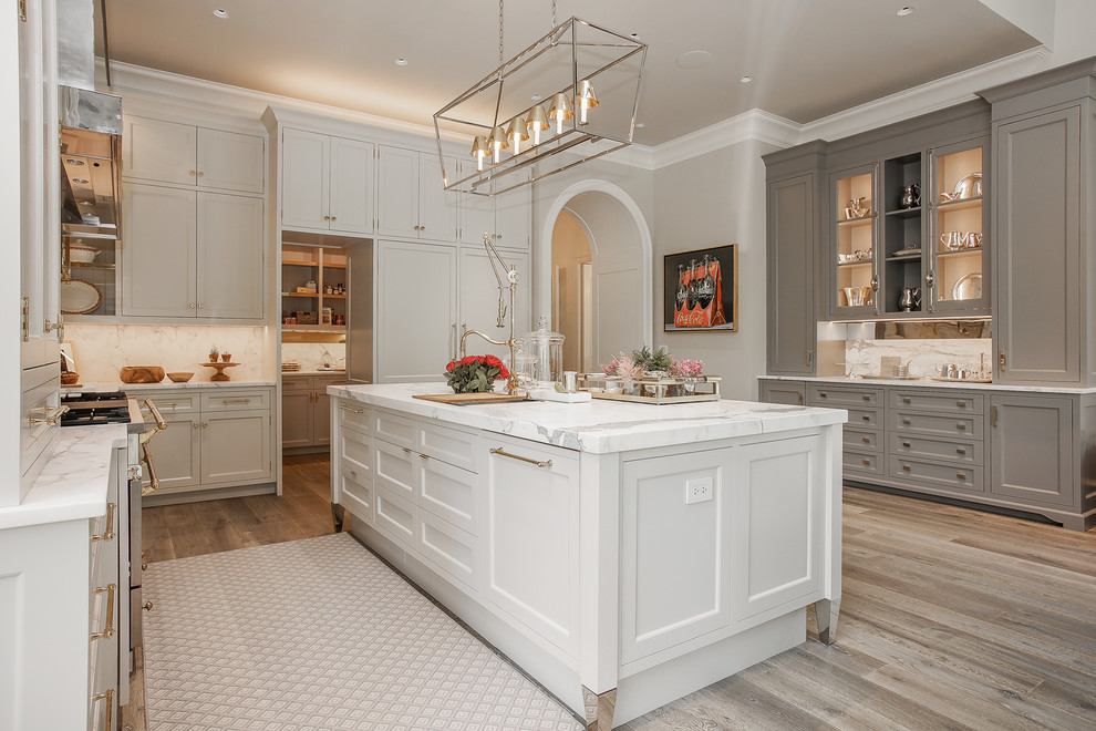 Kitchen - traditional l-shaped dark wood floor and brown floor kitchen idea in Chicago with recessed-panel cabinets, gray cabinets, white backsplash and stainless steel appliances