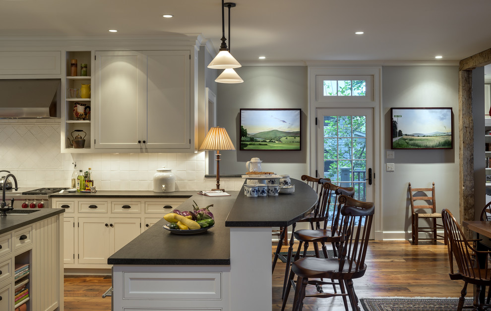 Elegant eat-in kitchen photo in New York with shaker cabinets, beige cabinets, stainless steel appliances and white backsplash