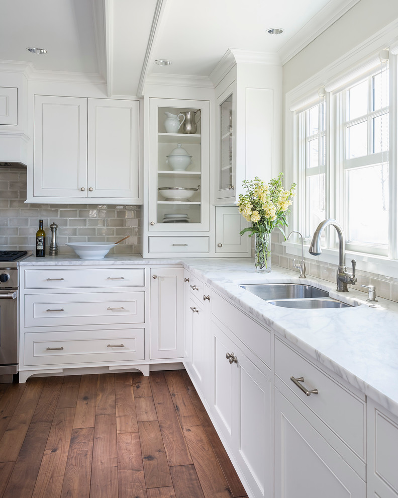 Mid-sized elegant l-shaped dark wood floor kitchen photo in Minneapolis with an undermount sink, recessed-panel cabinets, white cabinets, marble countertops, gray backsplash, ceramic backsplash, an island and stainless steel appliances