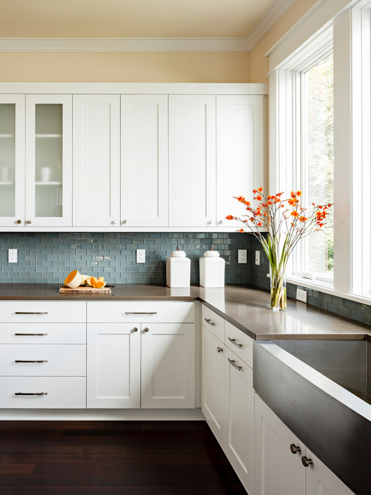 Enclosed kitchen - mid-sized transitional l-shaped dark wood floor enclosed kitchen idea in Portland with a farmhouse sink, blue backsplash, white cabinets, shaker cabinets, quartz countertops, an island, brown countertops, mosaic tile backsplash and stainless steel appliances