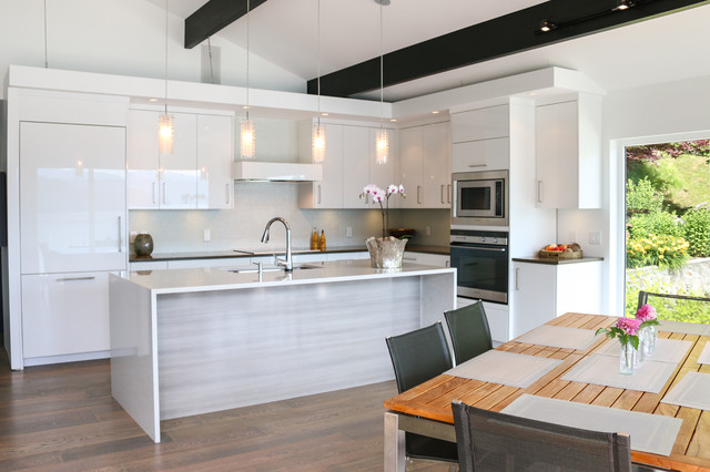 Inspiration for a mid-sized modern l-shaped medium tone wood floor kitchen remodel in Vancouver with flat-panel cabinets, white cabinets, quartz countertops, an island, an undermount sink, stainless steel appliances and glass tile backsplash