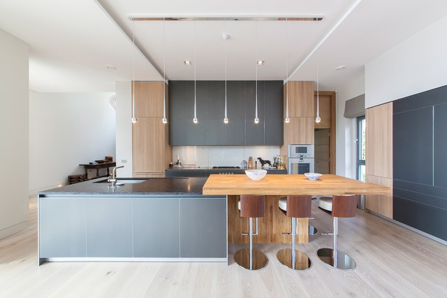 Design ideas for an expansive contemporary open plan kitchen in Surrey with light hardwood flooring, an island and a submerged sink.